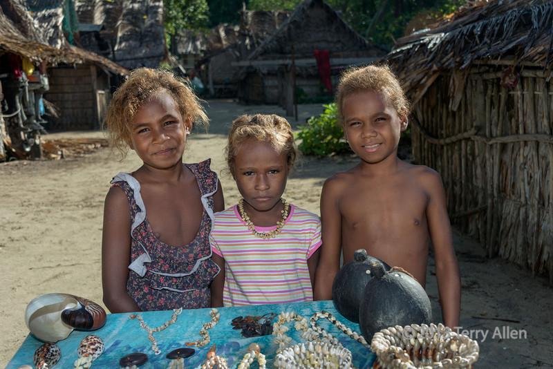 Three children selling shells, Santa Ana Island, Solomon Islands