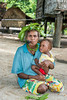 Woman smoking pipe and holding baby, Utupua Island, Solomon Islands