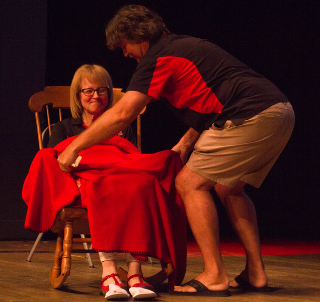 Steven Holmes wraps Liz in a blanket while seated in a rocking chair.