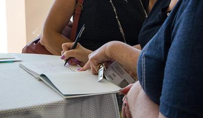 Judy Ahl signs Liz Rozell's retirement book.
