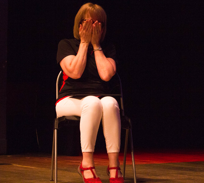 Liz Rozell covers her face after being forced to sit at center stage in the Indoor Theater.