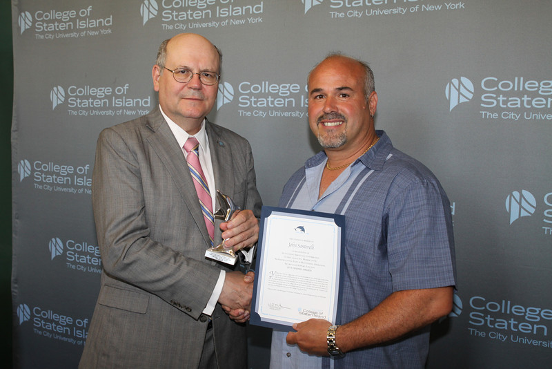 Dolphin Award for Outstanding Service and Contribution to the College by a Member of the Non-Instructional Staff in Maintenance, Operations, Security, and Support Function:<br /> John Santorelli, Supervisor of Plumbers, the Office of Buildings and Grounds<br /> <br /> You have been with the College since 1995. You are responsible for the complex task of supervising not only the College's plumbers, but also the work of outside contractors. In addition, you assist with on-campus projects, and respond to emergencies. Although you handle all of these tasks with the utmost efficiency and professionalism, your friendly demeanor and willingness to go above and beyond make you a true asset to the College. You are also happy to pitch in and help fellow workers in other trades, for example, carrying wood, hanging large fixtures, or even clearing snow, all to ensure a safe and clean environment for everyone at this College to work and study. <br /> <br /> Today, we salute your determined commitment to keeping our campus running smoothly and efficiently.