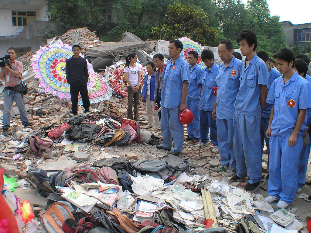 Construction workers from outside were paying their condolence in front of the memorial with school bags piling up at the Fuxin Second PS.