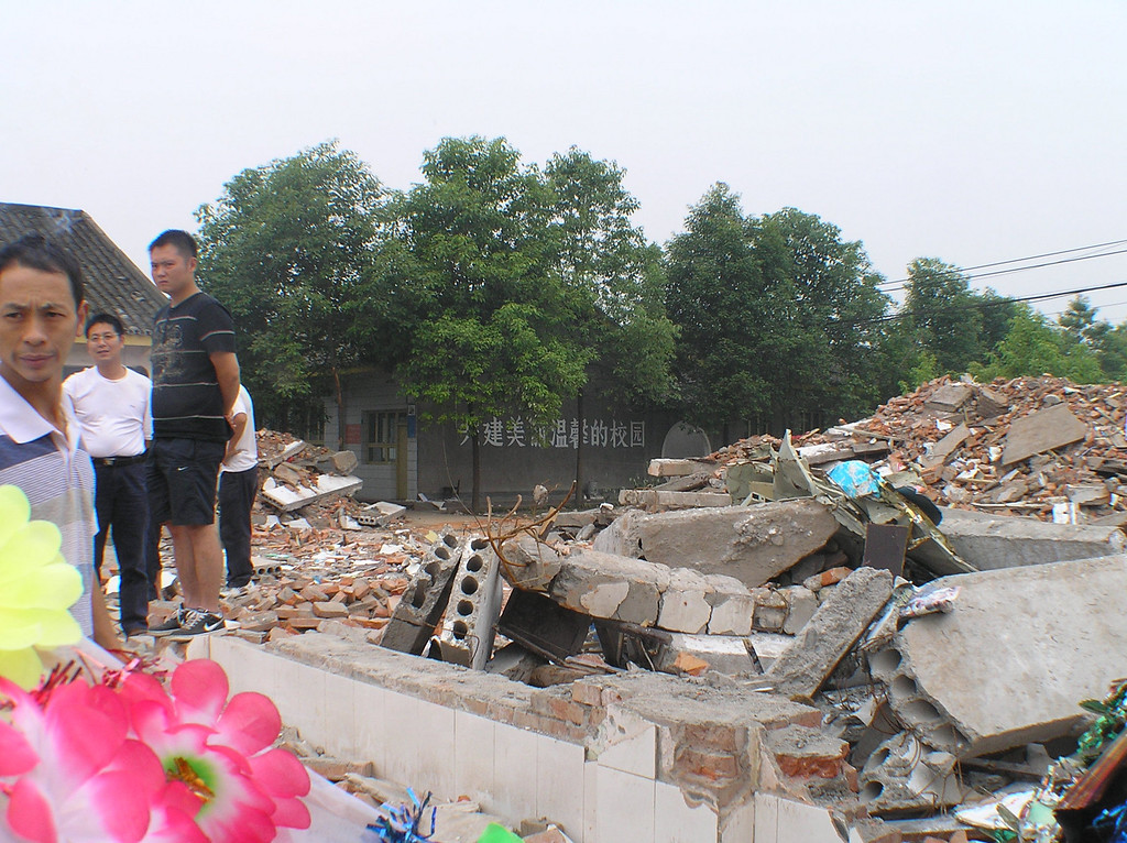 "In the township of Fuxin, Mianzhu, the teaching building of Fuxin Second Primary School collapsed and killed 127 students. Looking over the piles of slabs and bricks, the slogan reads: ""Working together to Build a Beautiful and Nurturing Campus."""