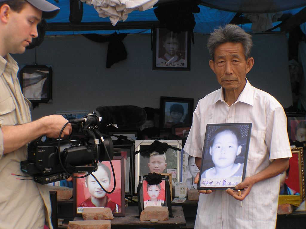 A grandpa was holding the picture of his grandson, Fu Hao, while Matt O'Neill was filming.