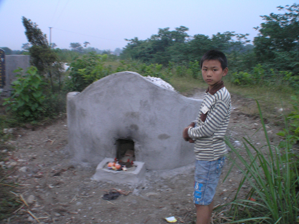 A boy, who luckily escaped from the collapsing building at the Fuxin Second PS, was standing in front of the newly built grave of his cousin.
