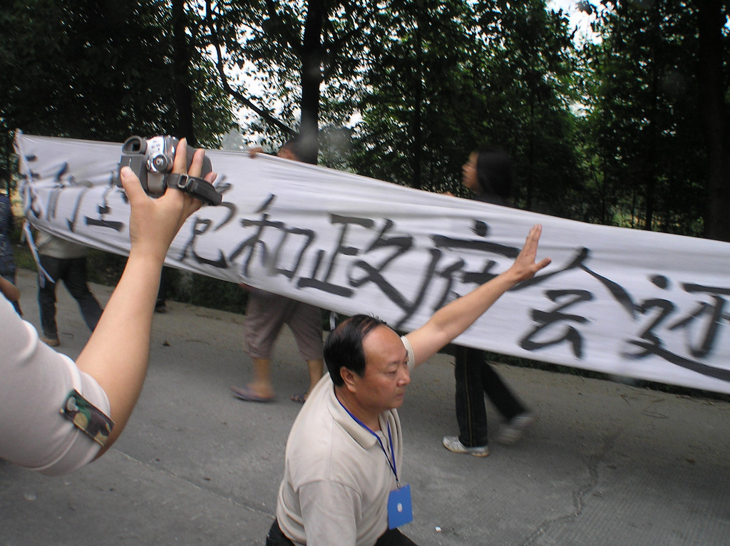 "Mr. Jiang Guohua, the Party Secretary and the Chairman of the City Congress in Mianzhu, was kneeling down to beg the parents not to continue the march. The banner carried by the parents reads: ""We Believe that the Party and the Government will Give Us Justice!"""