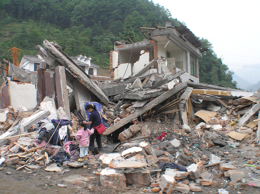 In the township of Hongbai, Shifang, a mother and her daughter were trying to rescue some clothes from their collapsed house.