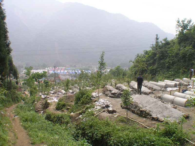 Jon Alpert was filming, as many parents were still searching for their children's graves, since many of them were migrant workers away from home as the earthquake hit. The new graves reach all the way to the highway downhill.