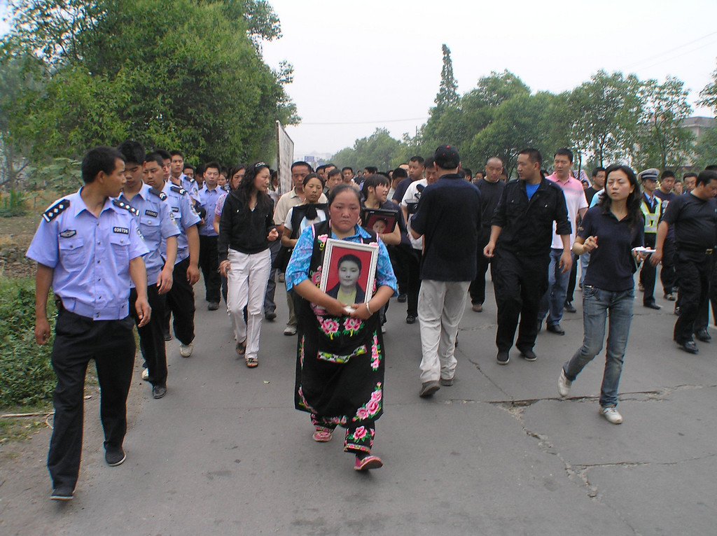 A woman dressed in Qiang minority nationality outfit, led the march and was flanked by policemen.