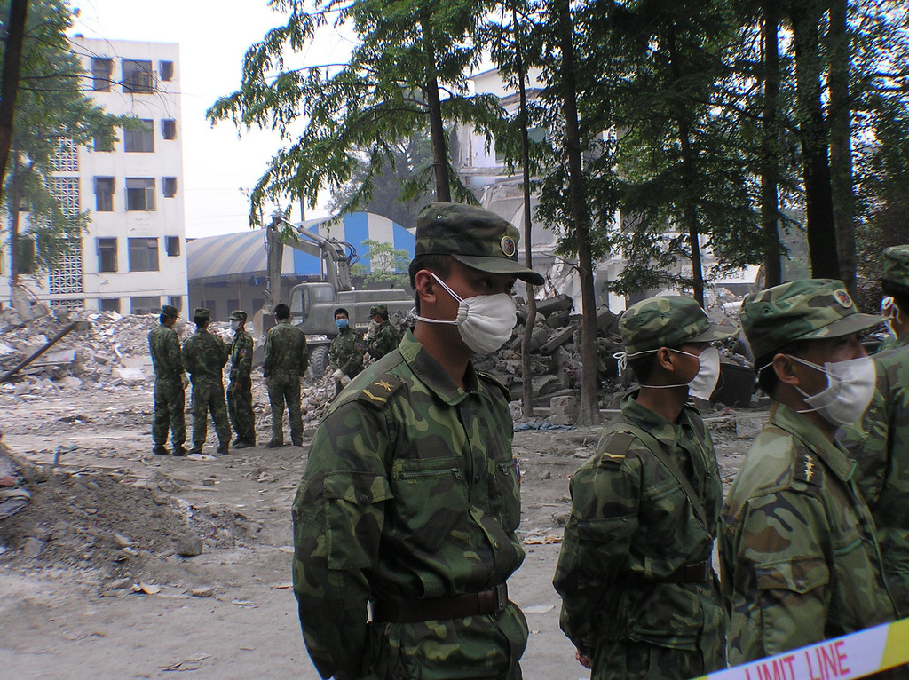 At Juyuan High School in a township near the city of Dujiangyan, the soldiers were dispatched to guard the collapsed school building and to keep off the parents, onlookers, and journalists, as the digging for bodies was going on.