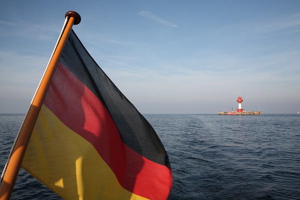02.10.2011, Kiel, ein Segeltoern in der Kieler Bucht. Eine Deutschland-Fahne am Heck einer Segelyacht, im Hintergrund der Leuchtturm Kiel. Dieser steht vor der Kueste in der zentralen Kieler Bucht vor Kiel als Leit- und Orientierungsfeuer und beherbergt neben zahlreichen Messeinrichtungen auch eine Lotsenstation.