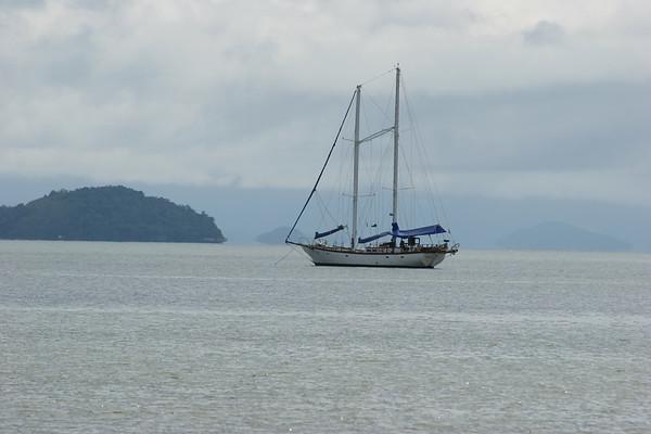 Paraty, Brasilien, ein Segelboot liegt auf Reede in einer Bucht.