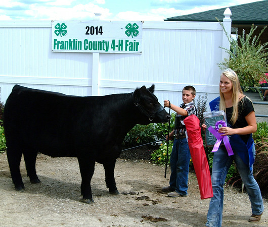 Christopher Aune | The Herald-Tribune<br /> Fair royal Megan Hensley (right) presented a ribbon to Tim Ludwig, whose animal won the Reserve Grand Champion Market Animal in the Beef Show.