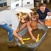 Diane Raver | The Herald-Tribune<br /> Jenna Honnert (from left), 11, Batesville; Maggie Sizemore, 13, Cincinnati; and Kelly Glardon, 10, Metamora, enjoy digging for potatoes at the Farm Bureau booth.