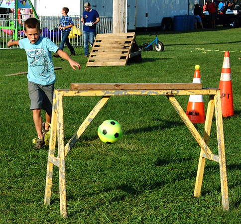 Debbie Blank | The Herald-Tribune<br /> Peter Schuster, 8, West Harrison, kicks a soccer ball between the sawhorse during the timed obstacle course contest.
