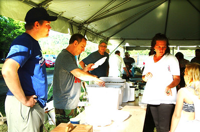 Debbie Blank | The Herald-Tribune Pork Producers of Knights of Columbus Council 1010 (from left) Winston Kunkel, Bob Jonas and Ronnie Bruns serve pork chop dinners to Mary Ellen King, Brookville, and a child.