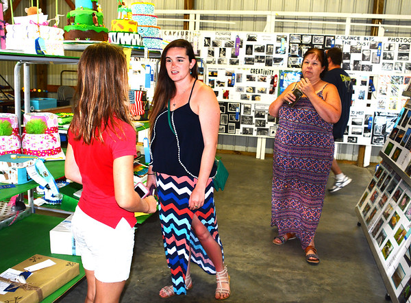 Debbie Blank | The Herald-Tribune<br /> Batesville friends (from left) Kylie Jones, 10; Katilyn and mom Ceil Miller chat while admiring 4-H members' exhibits. Jones won an honor award for her banana oat muffins.