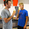 Debbie Blank | The Herald-Tribune<br /> Caleb Moster (right), 17, who likes to enter photography projects, and dad Sebastian, Batesville, take a break from the sweltering heat to savor ice cream cones. The Indiana Farm Bureau booth raises money for scholarships, this year received by Wade Volk, Sarah Pitts, Kirsten Weber and Morgan Weber.