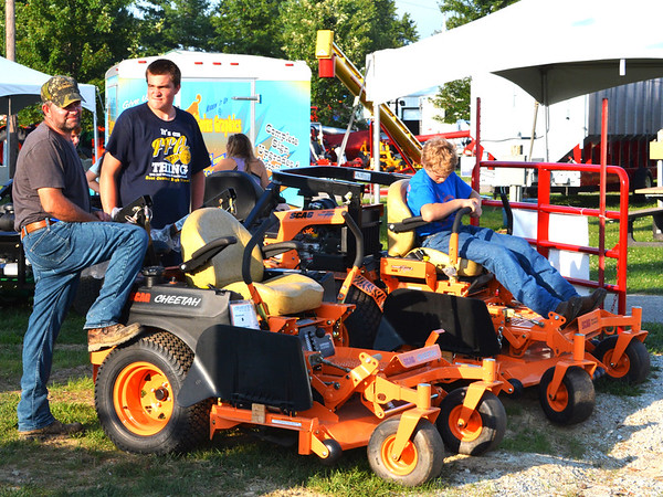 Debbie Blank   The Herald-Tribune<br /> Farm equipment attracted the attention of Jim Rennekamp (from left), Sunman, his son Jimmy, 15, and Theo Martini, 15, Sunman. The boys' favorite 4-H projects are welding and small engines, respectively.