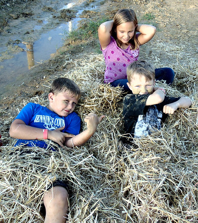 Diane Raver | The Herald-Tribune<br /> Holton residents Jayden Minneman (counterclockwise from bottom left), 6; Abrahm Speer, 7; and Callie Comer, 8; took advantage of the busted bales of straw.