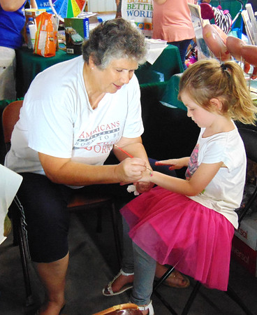 Diane Raver | The Herald-Tribune<br /> Mary Jean Wessel (left) paints a flower on the wrist of Halle Wendell, 5, Batesville, at the Respect Life booth.