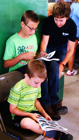 Debbie Blank | The Herald-Tribune<br /> Brothers Nathan (upper left), 11, and Logan Voss, 4, Milan, and their mom were among about 100 spectators at the 2018 Ripley County 4-H Beef Show July 25. Nathan's favorite part of the fair is showing animals, especially his goats.