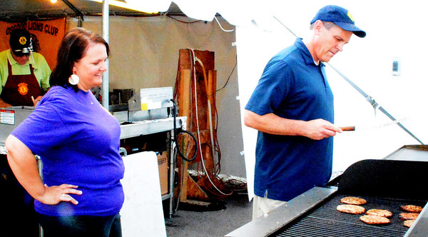 Debbie Blank | The Herald-Tribune<br /> Sister and brother Tonya and Mike Hughes grill porkburgers at the Osgood Lions Club booth. Proceeds are used for community and school activities.