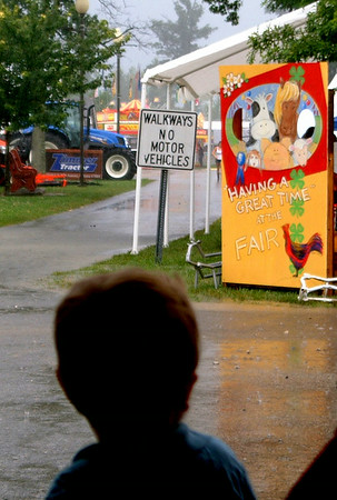 Christopher Aune | The Herald Tribune<br /> Rain fell hard and long at the fair Wednesday night, encouraging families to tour the 4-H exhibit barns. The fair continues through this Saturday, July 26.