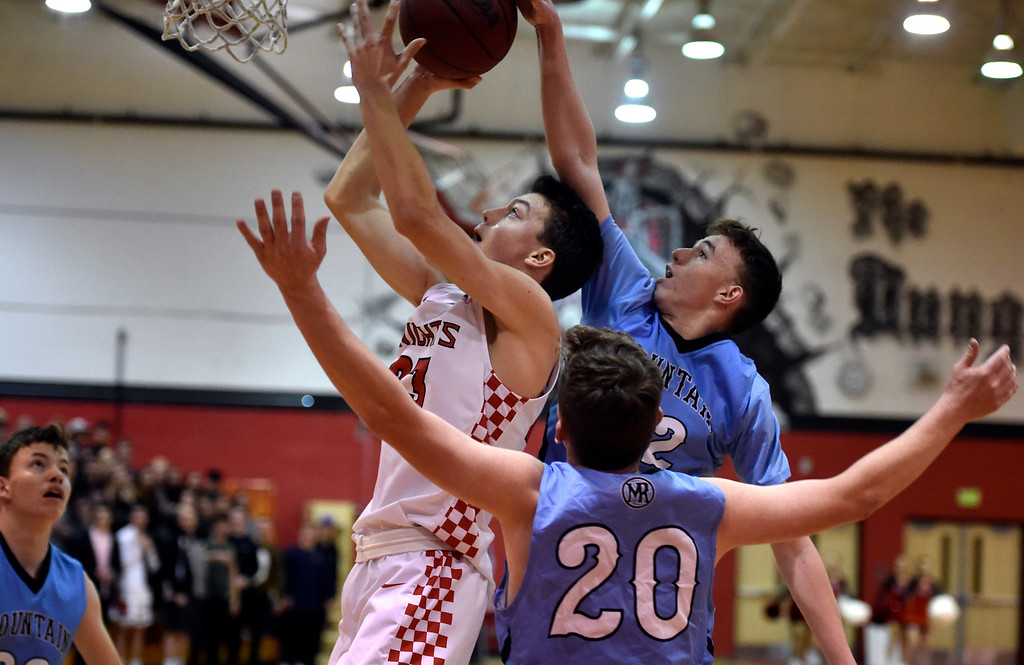 . BOULDER, CO - JANUARY 11, 2019: Fairview High School\'s Greyson Carter drives to the hoop over a swarm of defenders during a CHSAA basketball game against Mountain Range on Friday in Boulder. More photos: BoCoPreps.com (Photo by Jeremy Papasso/Staff Photographer)