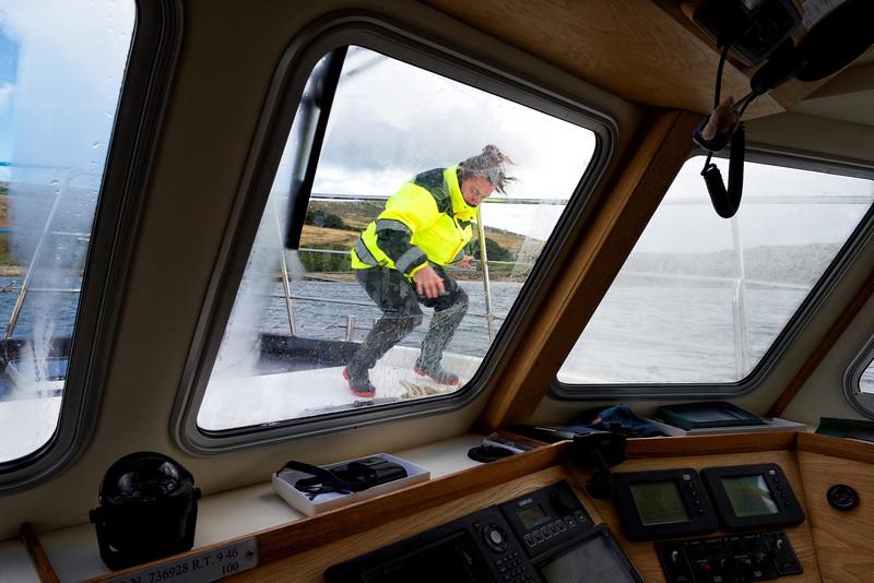 """Nikki Summers déséquilibrée par une rafale de vent sur le pont du """"Seaquest"""" au moment de l'accostage à West Point Island/ Iles Falkland (Iles Malouines)"""