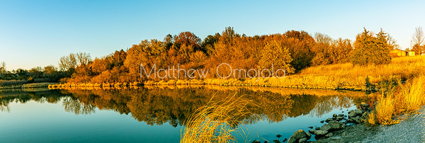 Panorama Fall autumn reflections. Fall color reflection in water. Brown foliage marking end of autumn, Beautiful reflection in lake . Sunset glow on the brown foliage and lake.