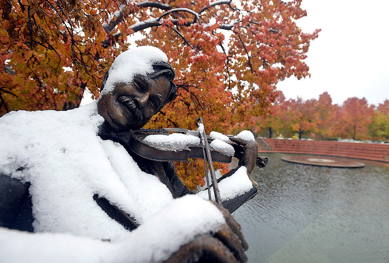 "Snow covers a bronze sculpture ""Joy of Music"" by George Lundeen Monday, Oct. 9, 2017, at Foote Laggon downtown in Loveland.  (Photo by Jenny Sparks/Loveland Reporter-Herald)"