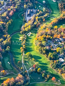 Golf Course surrounded by fall colors aerial view.