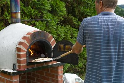 Jetzt geht die erste Pizza in den Ofen.