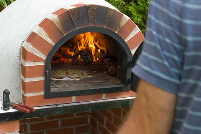 Mann muss die Pizza ab und zu drehen, damit sie gleichmässig gebacken wird.