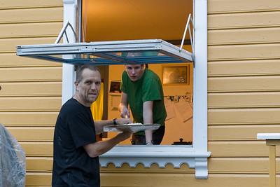 Bernd ta imot pizza foran kjøkken.