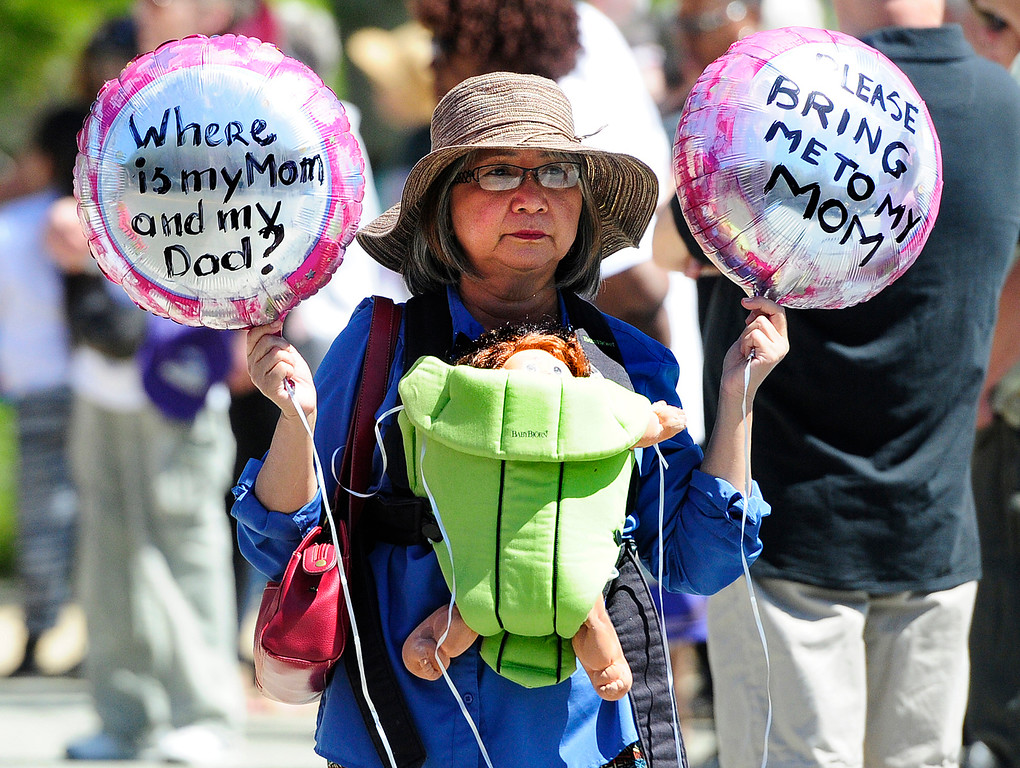 . VALLEJO, CA - JUNE 30, Yoly Ejanda holds balloons in front of the JFK Library as she carries a baby doll to protest President Trump\'s immigration policies during Families Belong Together rally on Saturday in Vallejo.The rally took place with thousands of others nationwide. (CHRIS RILEY/TIMES-HERALD)