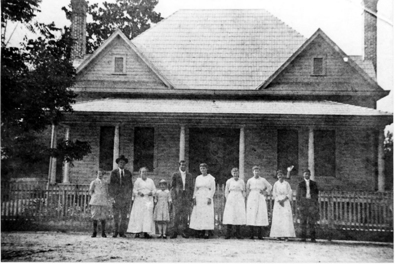 T. J. Crum family in front of their home. <br /> Left to right: John C., Jack, Annie, Lillie, Hill, Della, Mae, Mary, Delilah Gaskins and her son Lester Gaskins. Delilah was the sister of Annie Crum.<br /> Photo courtesy of Ben Hill Crum, Jr.