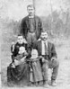 Rev. John David Mathis and Ellen Sutton family about 1896. Small girll in foreground believed to be Lola Mathis Allen who married Collis Allen. Other small child unidentified, man standing in rear also unidentified.