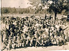Nash Family Reunion, in New Lois about 1945. <br /> Among those identified: Blonde child next to car headlight is Mack Terrell Nash, born 1942, held by his father, Calvin Bouie Nash. <br /> The lady just below the curly dark haired man by the tree is the wife of Mack Terrell, Nellie Lee Nash. <br /> The young lady just to her right is her daughter, Alene Nash Griner. And the young teen girl just in front left of her, is another daughter, Nelda Nash Smith.<br /> And just below her, a small blonde girl with her thumb in her mouth is Inell Griner Griffin, daughter of Alene Nash Griner. The older fellow with the black hat rolled up front is Ed Nash, the father of Calvin Bouie Nash. Other identifications needed.