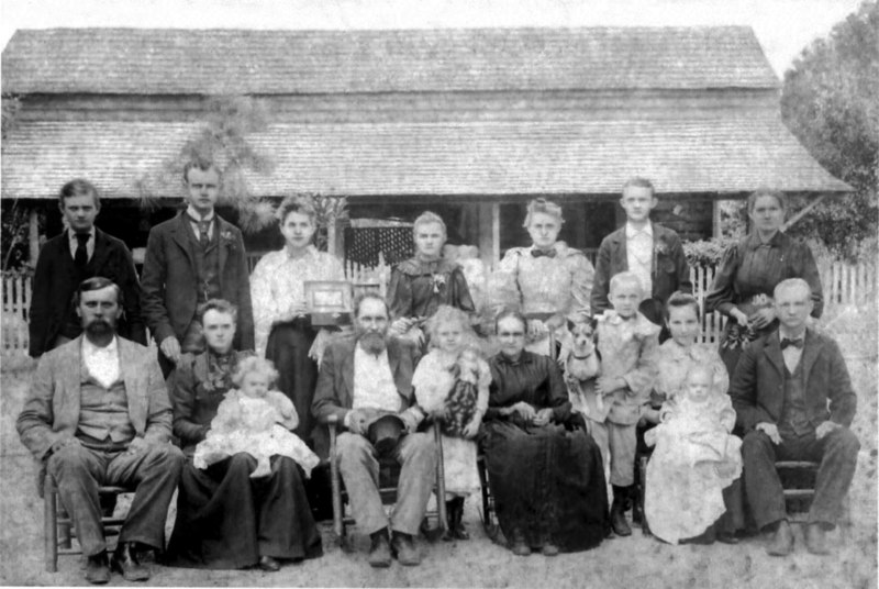 "The Mathew Patten family, about 1897. Sam and Matilda (seated at left) Bob and Maggie (seated at right) Others left to right: Walter, Bud, Effie in Matilda's lap, Kansas, Mathew, Fannie, Birdie, Martha, Maggie, Joe, John D., Lawson on Maggies lap, and ""Puss"" Fountain who was Martha's sister."
