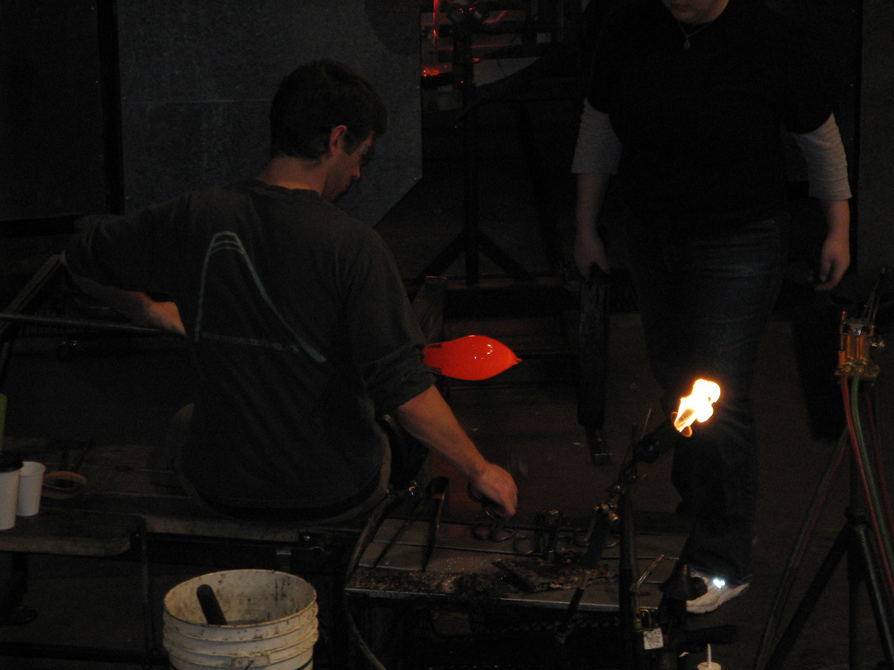 A glass artist is forming a red hot piece of glass into a work of art.