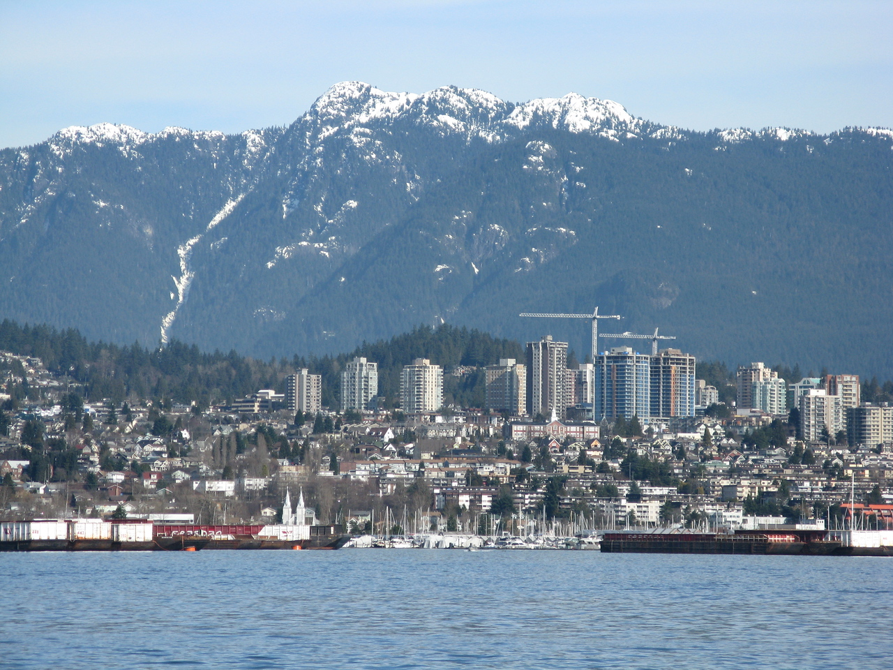 Looking across Burrard Inlet on the east side of Stanley Park to North Vancouver, a suburb framed by snow capped mountains.