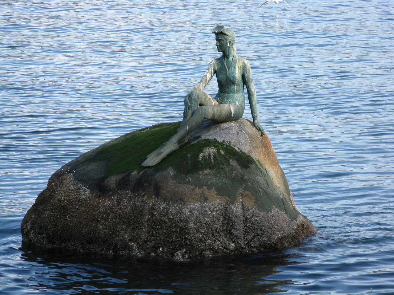 """Girl in a wet suit"" -- a statue perched on a rock on the east side of Stanley Park."