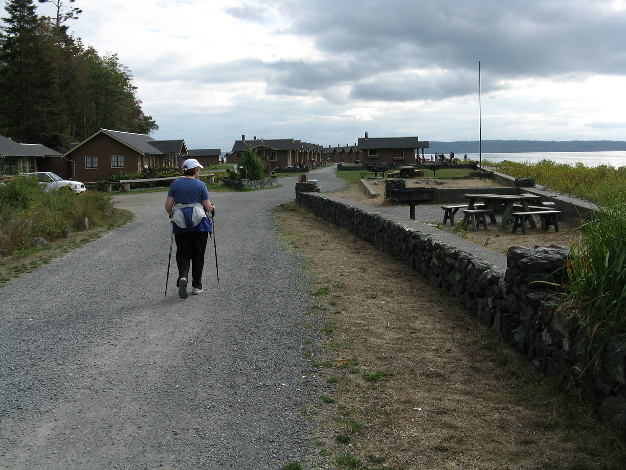 Mary is walking towards the smaller cabins at the beach.