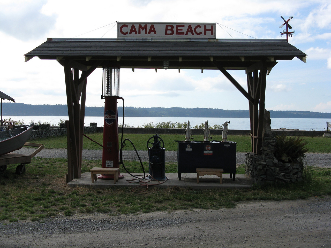 An antique gas pump with pumping handle,  back lit by the clouds and water.