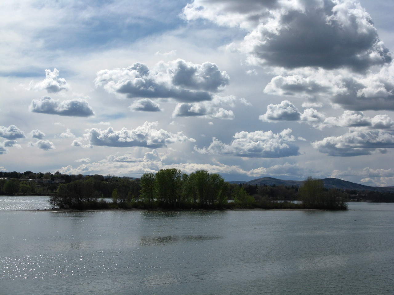 An island in the Columbia River with broken clouds above.