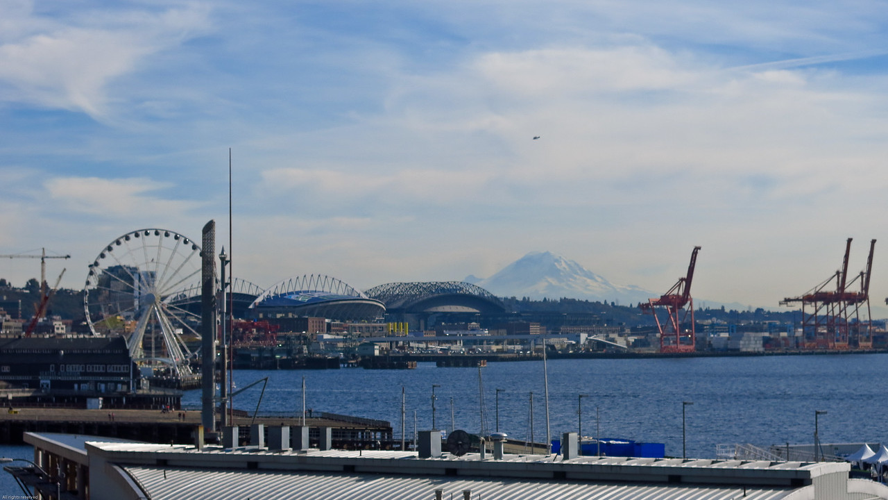 (L to R)  Great wheel, Centurylink Field (Seahawks football team), Safeco Field (Mariners baseball team), and Mount Rainier in the distance