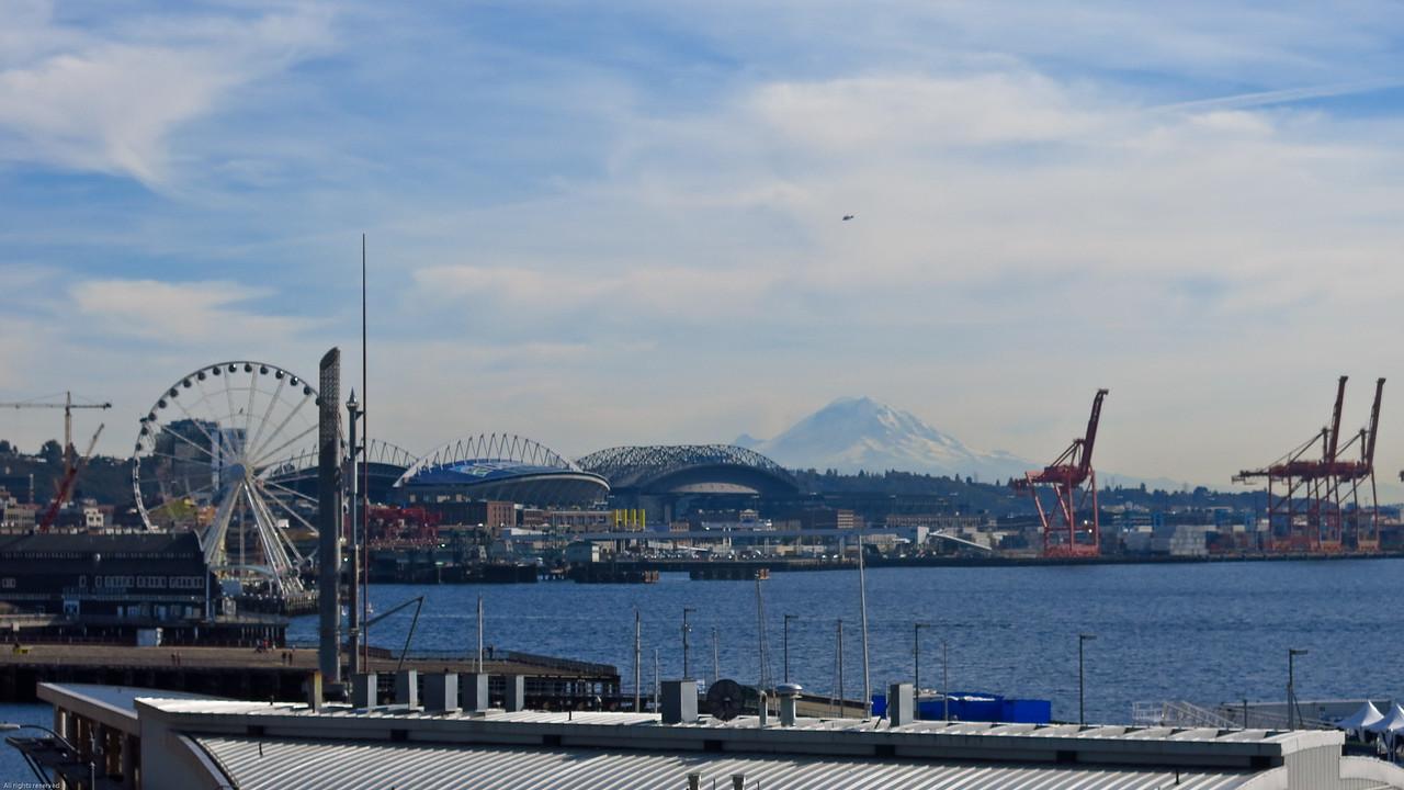 (L to R)  Great wheel, Centurylink Field (Seahawks football team), Safeco Field (Mariners baseball team), and Mount Rainier in the distance